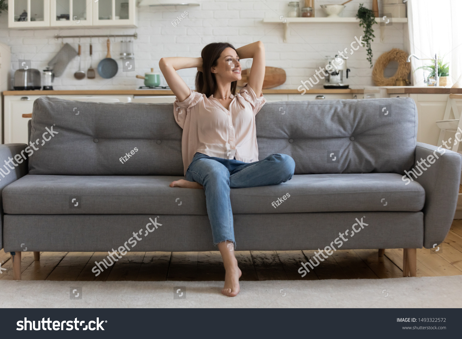 In cozy living room happy woman put hands behind head sitting leaned on couch 30s european female enjoy lazy weekend or vacation, housewife relaxing feels satisfied accomplish chores housework concept #1493322572
