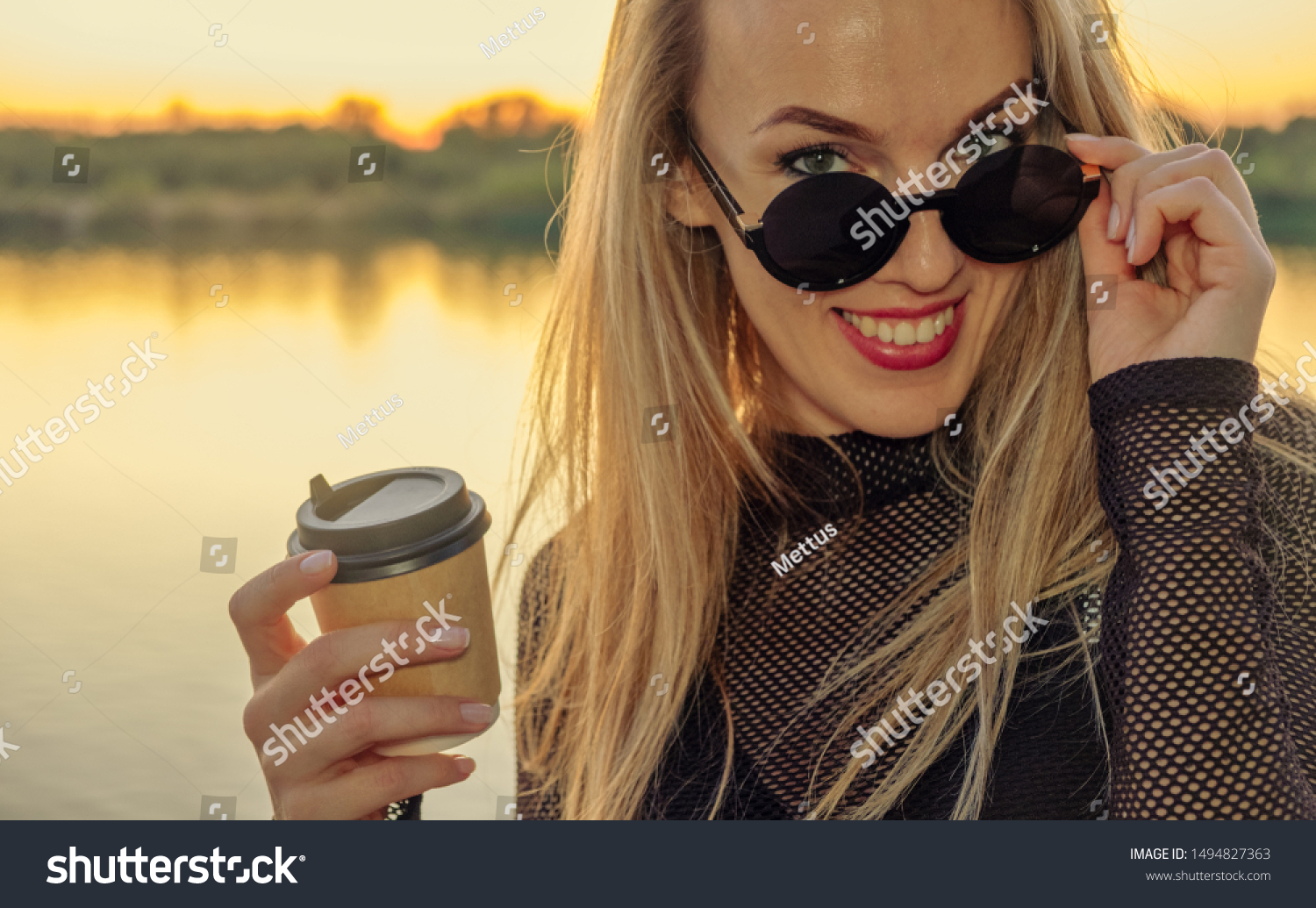 Closeup outdoor portrait of cute happy blonde Caucasian adult woman in happy state with takeaway coffee. Young woman with long hair wearing sunglasses in her 30s posing outside in front of sunset lake