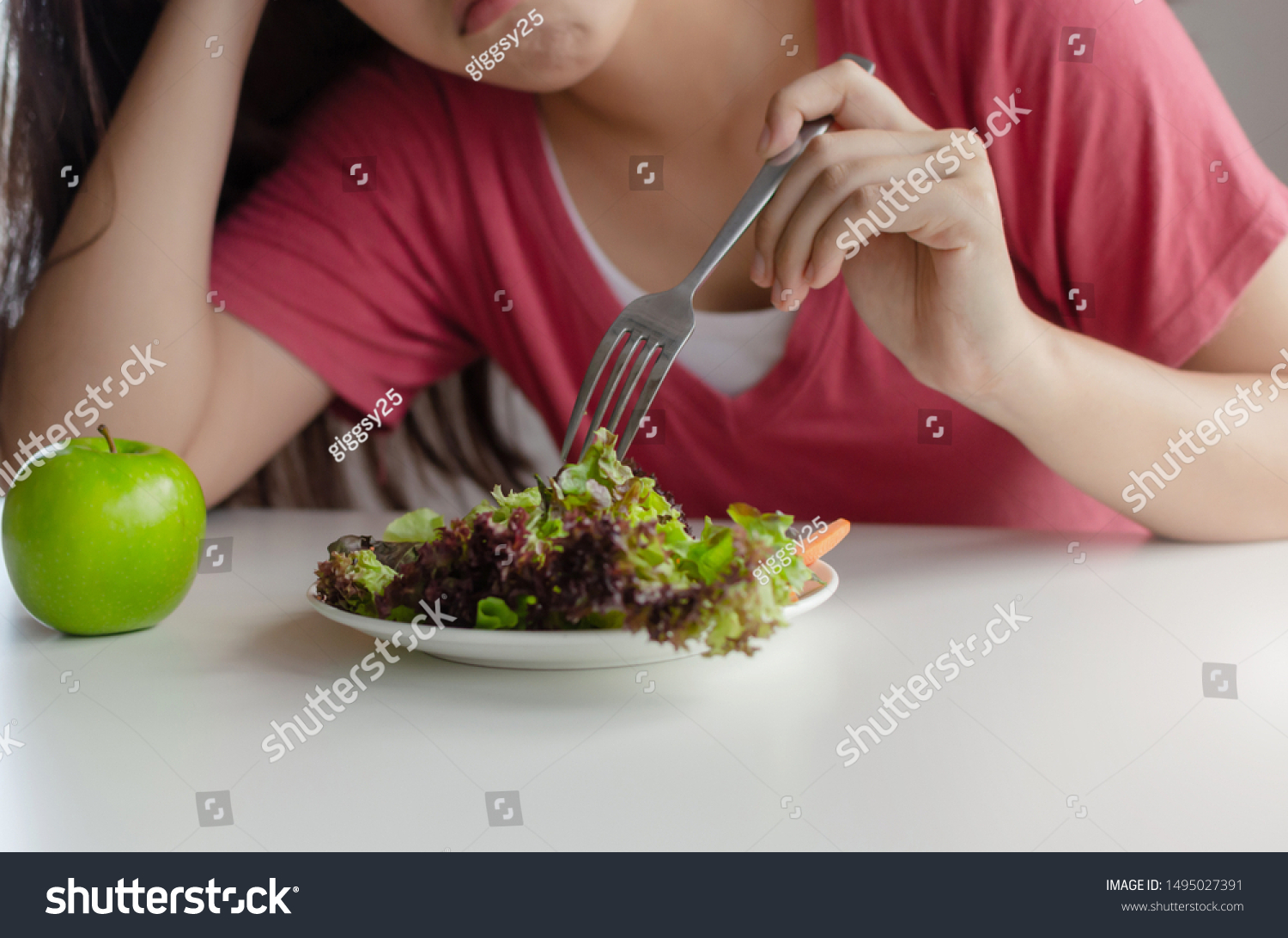 Diet. asian young pretty woman bored emotion and refuse for eating fresh green vegetables salad on table for good health at home, nutrition, weight loss, lifestyle, healthy food and dieting concept #1495027391