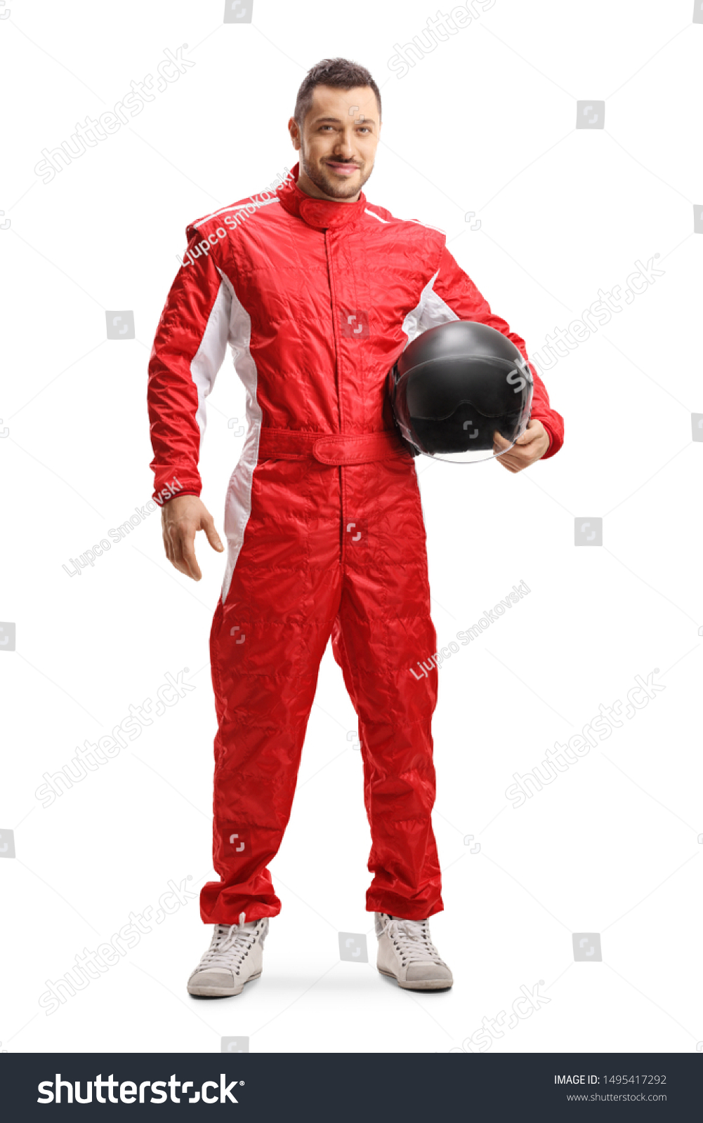 Full length portrait of a racer in a red uniform holding a helmet and smiling isolated on white background #1495417292