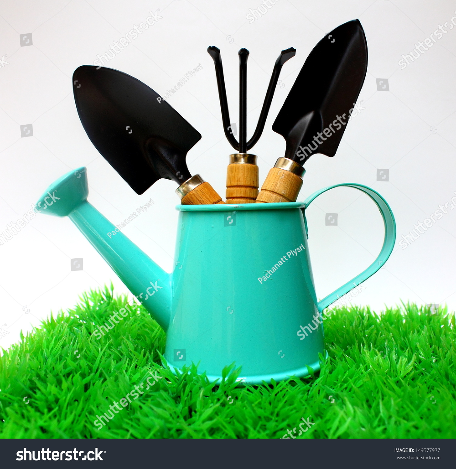 Gardening tools in watering can on grass on white for Gardening tools watering