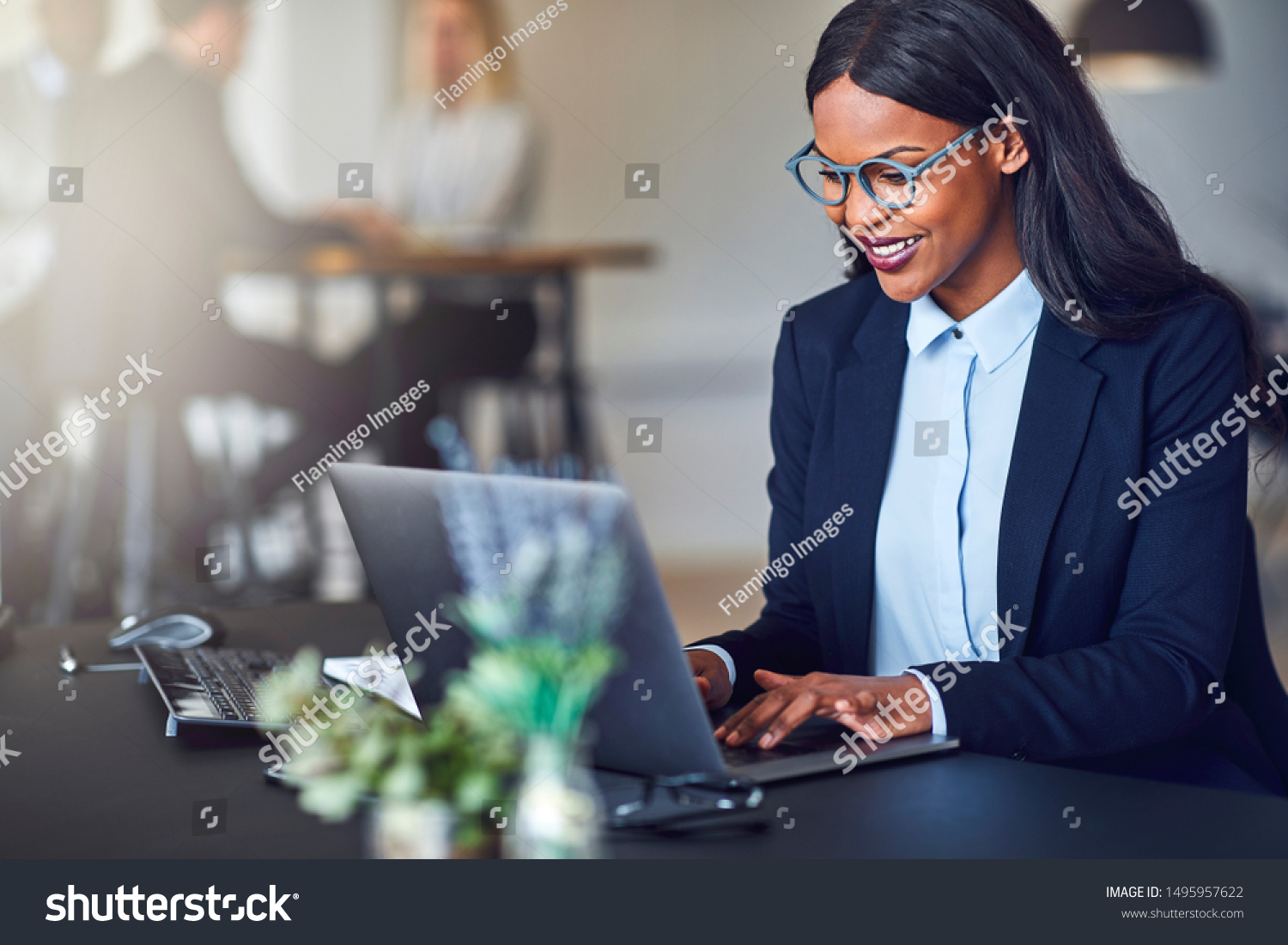 Smiling young African American businesswoman working on a laptop at her desk in a bright modern office with colleagues in the background #1495957622