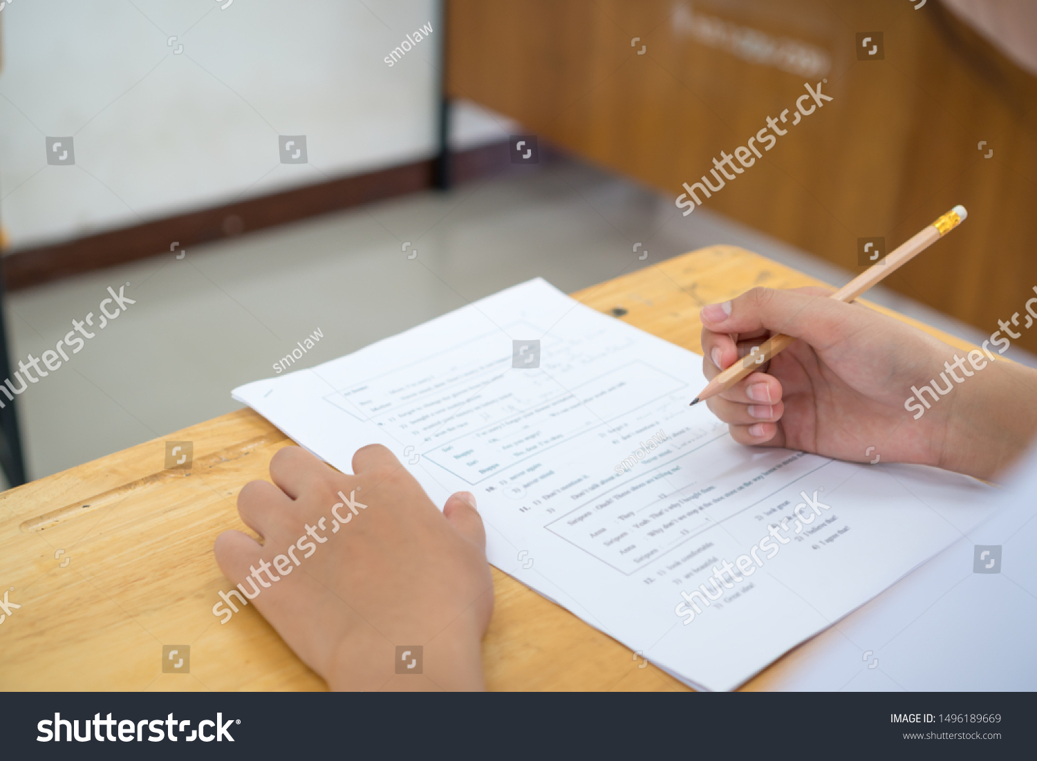 English exams test student in school, university students holding pencil for testing exam writing answer sheet or exercise for taking in assessment paper on table classroom. Education study Concept #1496189669