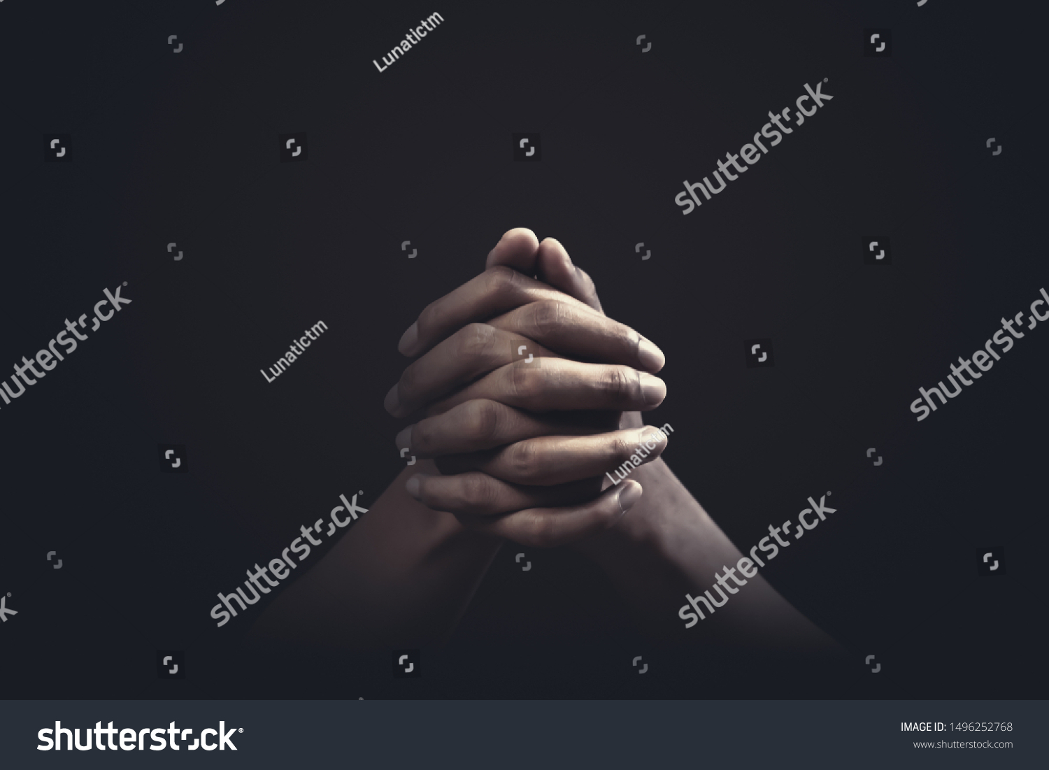 Praying hands with faith in religion and belief in God on dark background. Power of hope or love and devotion. #1496252768