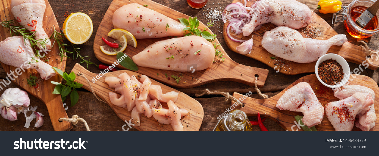 Panorama banner of raw chicken portions for cooking and barbecuing with skinless breasts and diced strips for goulash or stir fry with legs and wings with skin viewed from above with fresh seasoning #1496434379