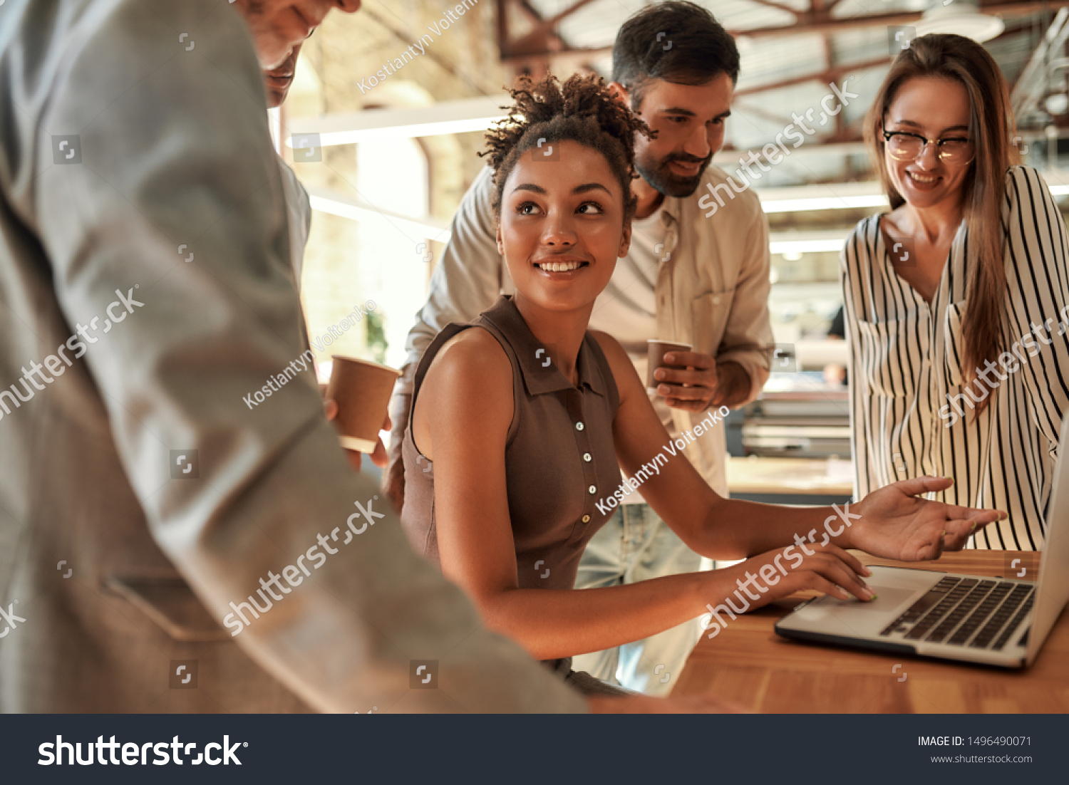 Working together. Young and cheerful afro american woman using laptop and discussing something with colleagues while sitting in the modern office. Teamwork. Office life #1496490071
