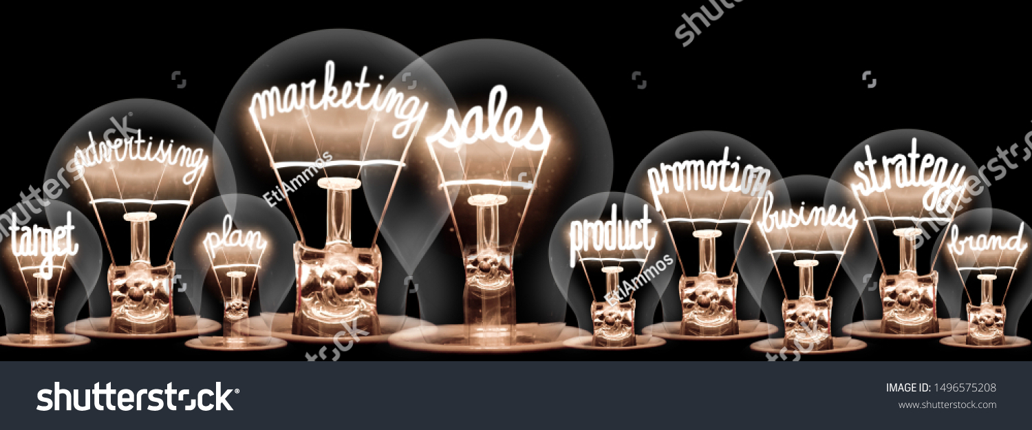 Photo of light bulbs with shining fibers in shapes of Marketing Sales, Advertising, Promotion and Strategy concept related words isolated on black background #1496575208