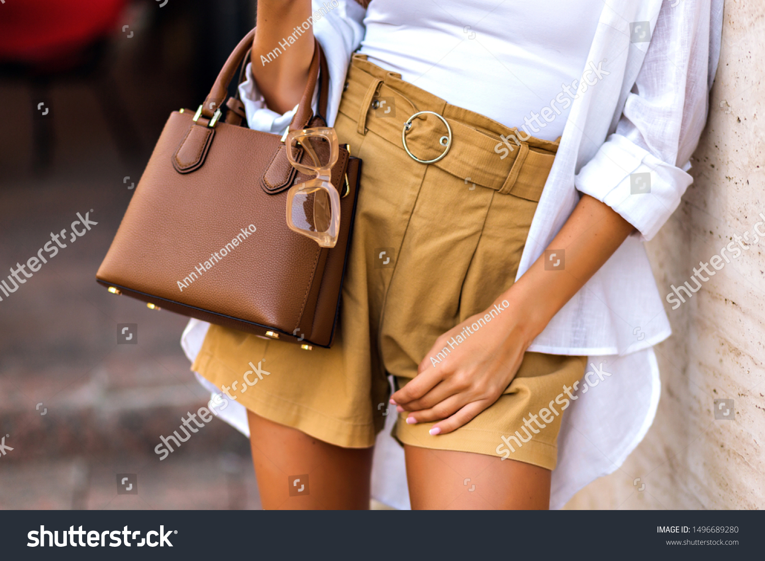 Street style fashion details, tanned woman wearing linen shorts, white shirt, brown leather bag and clear beige sunglasses, modern classic summer chic outfit, warm colors.