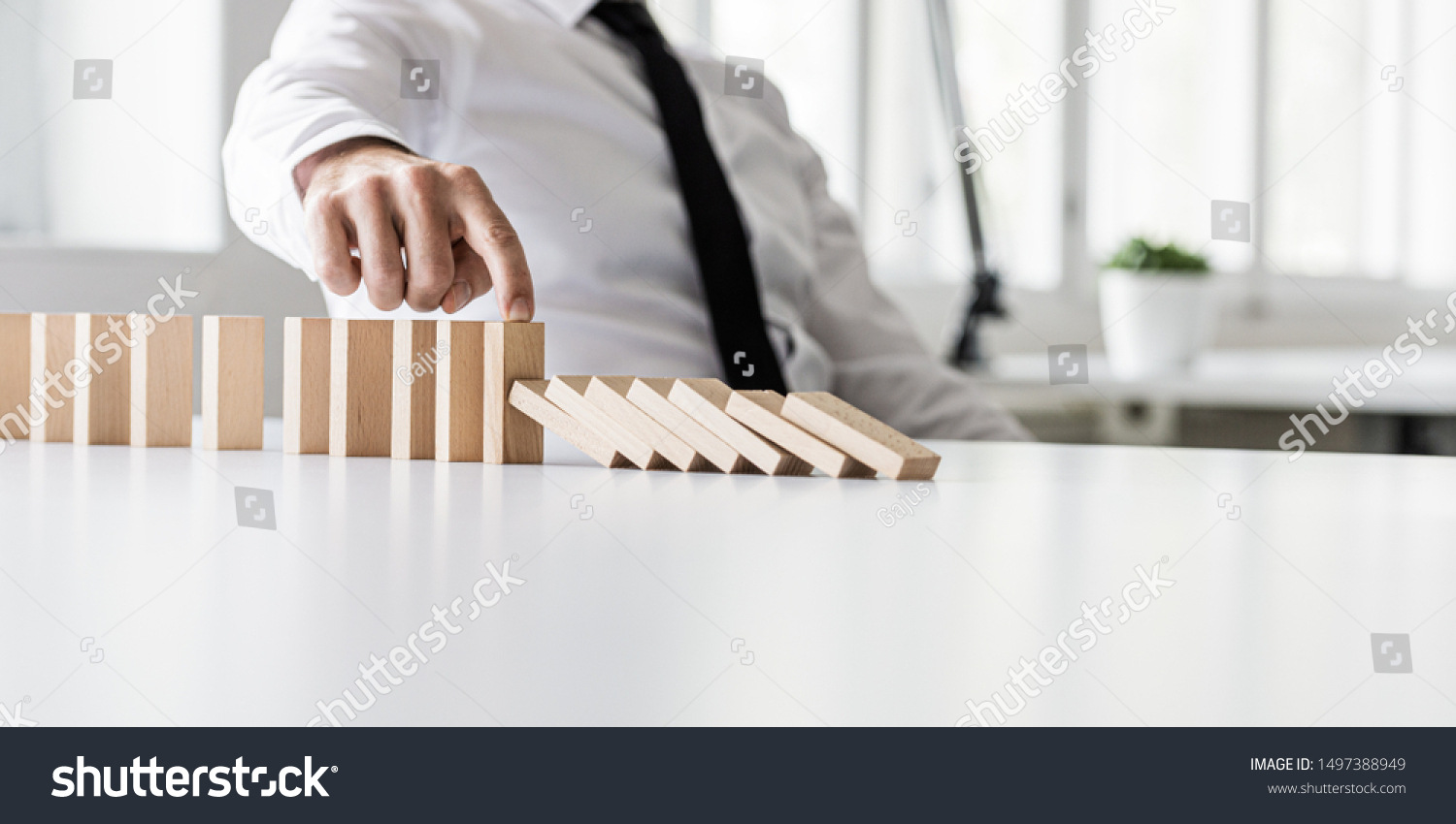Business crisis manager preventing wooden dominos to collapse in a conceptual image. #1497388949