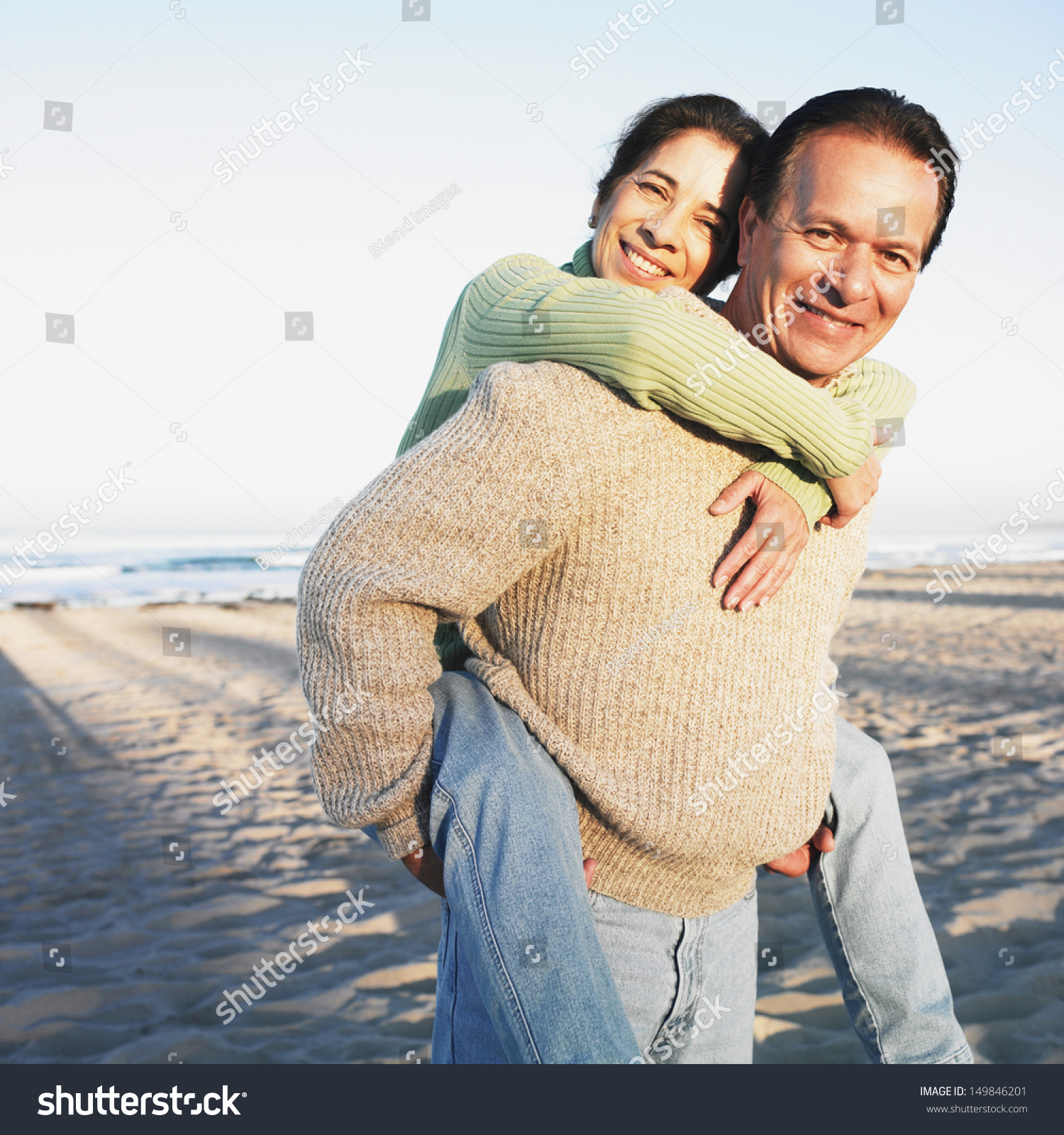Man Giving Wife Piggyback Ride At Beach Stock Photo