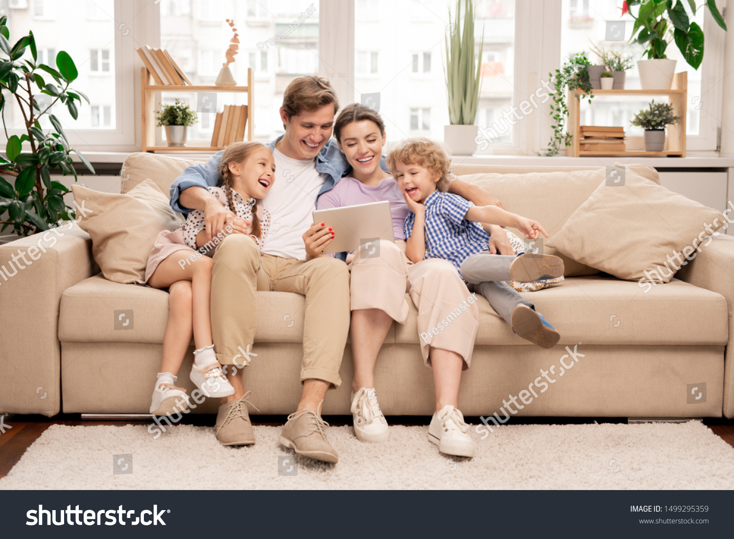Young joyful casual family of two kids and couple sitting on sofa and watching funny video or cartoons in touchpad #1499295359