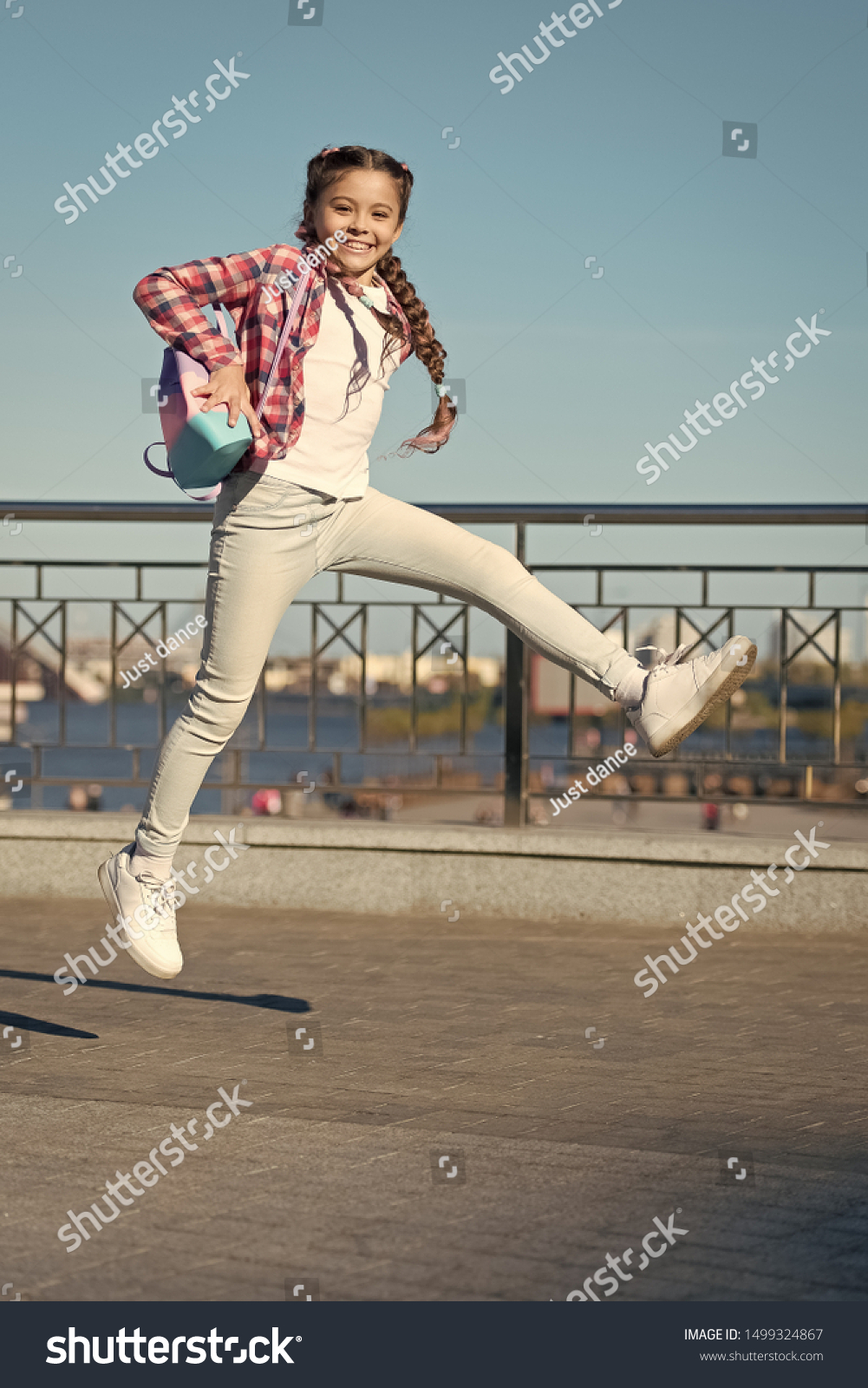 Being active outside. Active little child in motion on urban background. Happy small girl jumping active for pleasure. Active and energetic kid having fun in summer. #1499324867