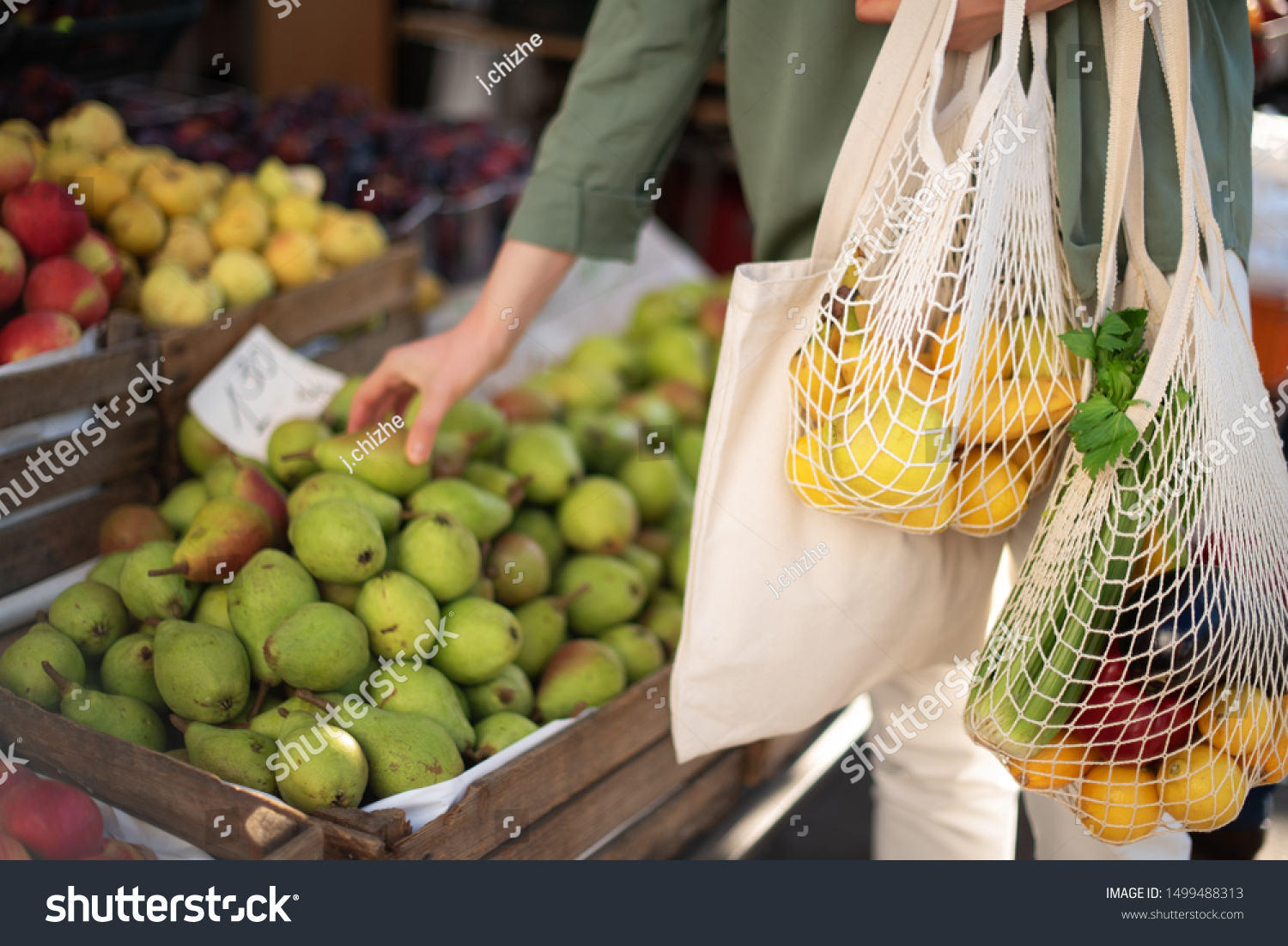 Woman chooses fruits and vegetables at farmers market. Zero waste, plastic free concept. Sustainable lifestyle. Reusable cotton and mesh eco bags for shopping #1499488313