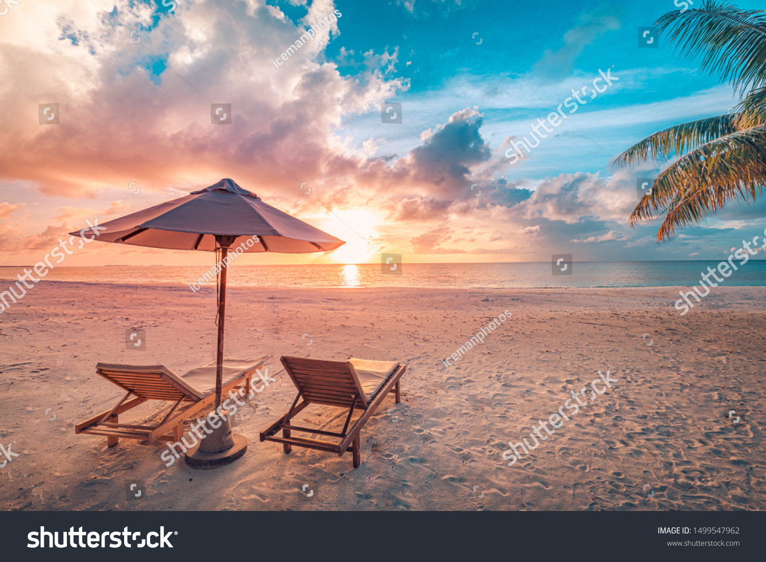 Beautiful tropical sunset scenery, two sun beds, loungers, umbrella under palm tree. White sand, sea view with horizon, colorful twilight sky, calmness and relaxation. Inspirational beach resort hotel #1499547962