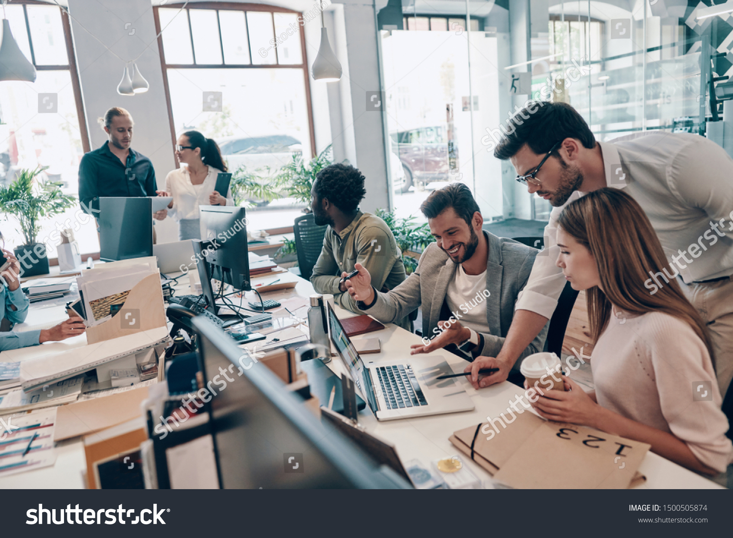 Group of young modern people in smart casual wear communicating and using modern technologies while working in the office              #1500505874