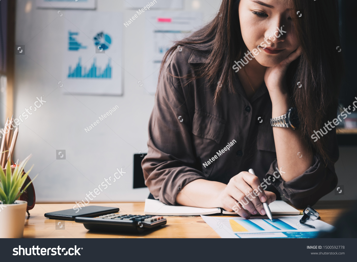 Business woman using calculator for do math finance on wooden desk in office and business working background, tax, accounting, statistics and analytic research concept #1500592778