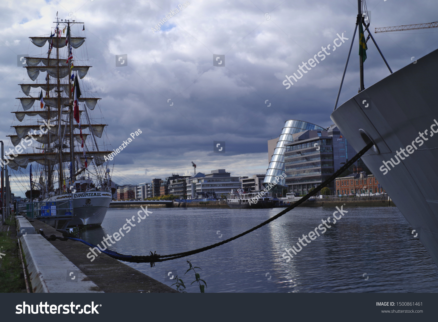 DUBLIN, IRELAND - SEPTEMBER 7, 2019: A view of the Convention Centre Dublin building. Navy ships and Liffey River in the front. Cloudy day.