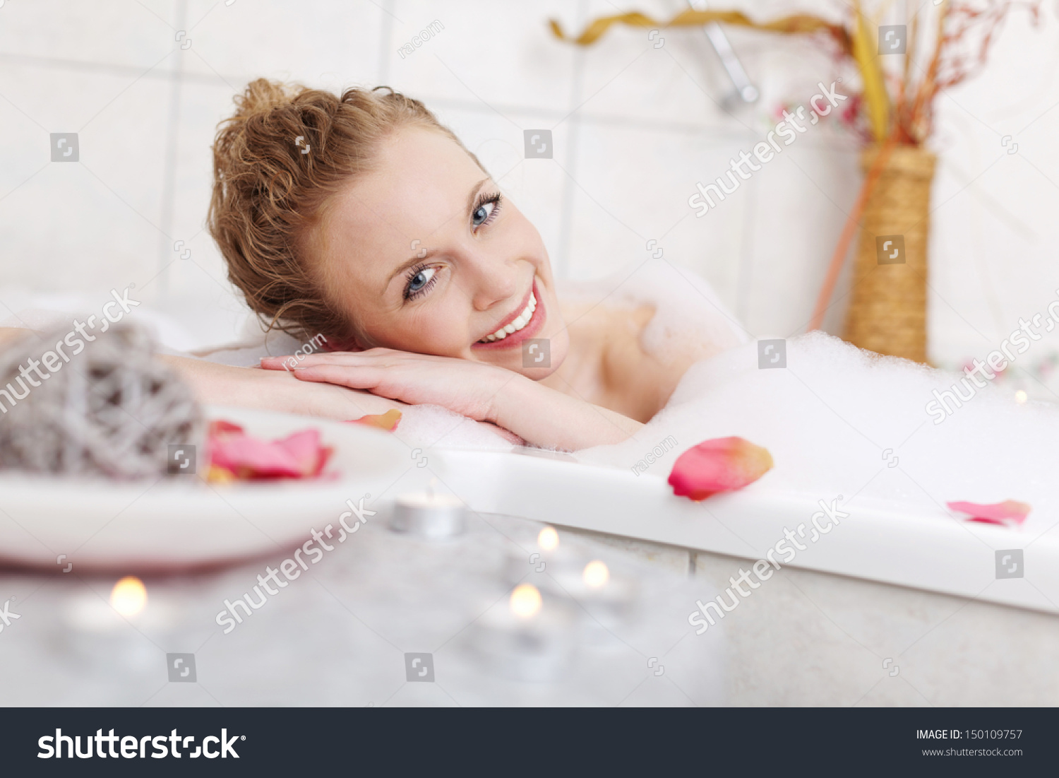 4b94566418 Beautiful woman relaxing in a foamy bubble bath resting her head on the  side and smiling