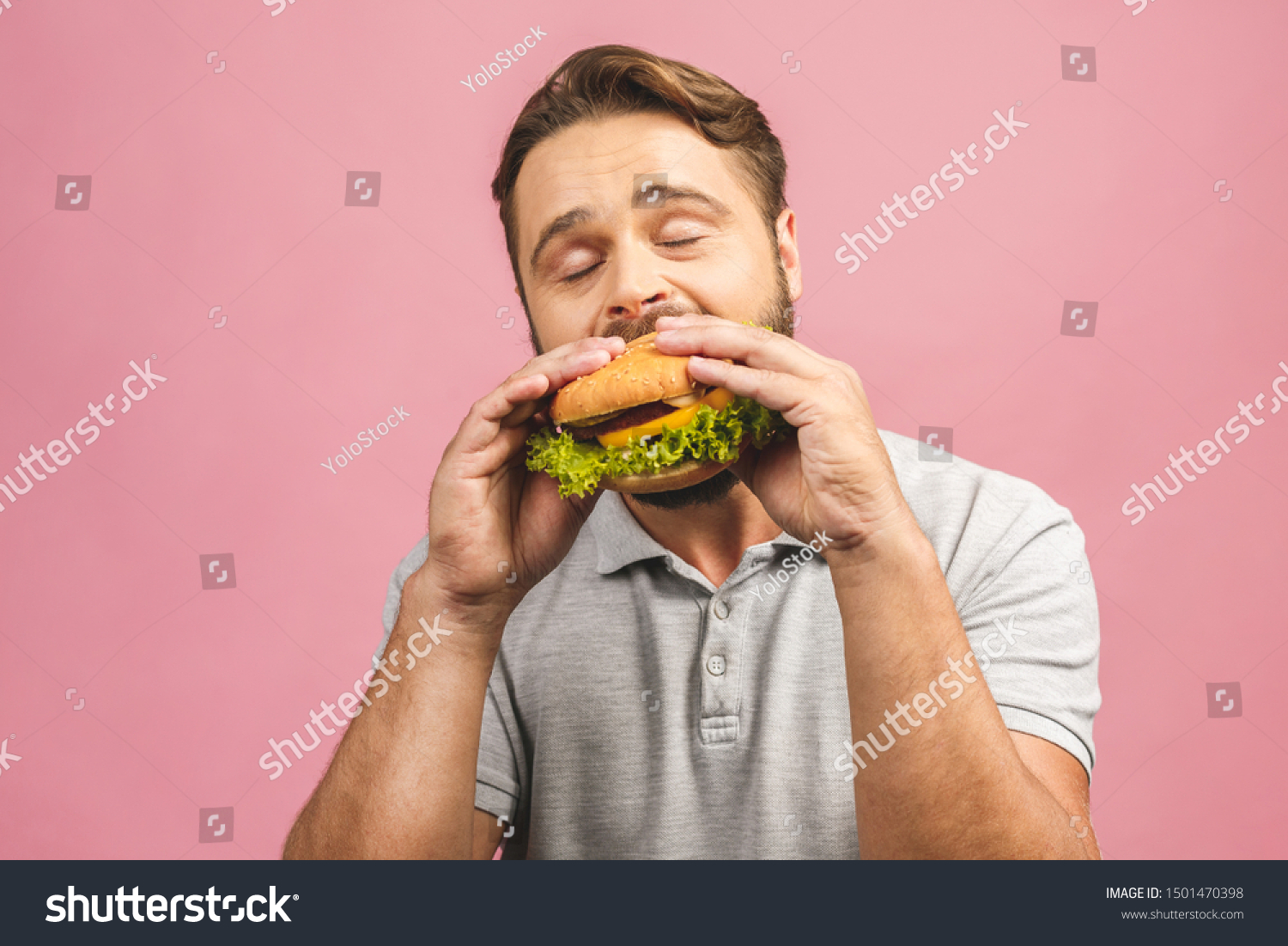 Young man holding a piece of hamburger. Bearded gyu eats fast food. Burger is not helpful food. Very hungry guy. Diet concept. Isolated over pink background. #1501470398