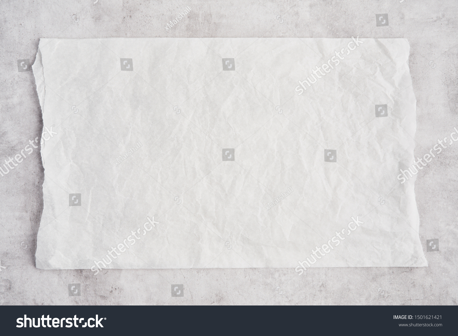 Crumpled piece of white parchment or baking paper on grey concrete background. Top view. Copy space for text and design element. #1501621421
