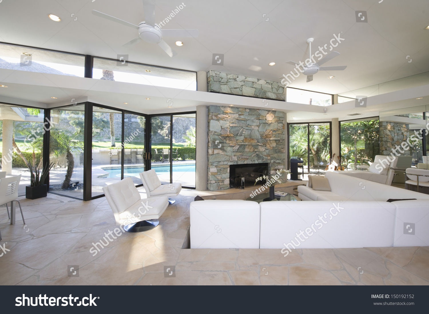 Sunken Seating Area And Exposed Stone Fireplace In Spacious Living Room With View Of Swimming Pool