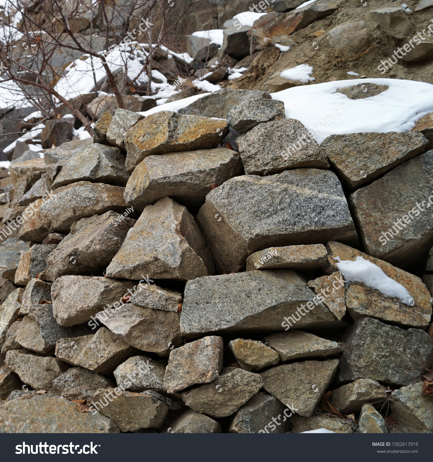 Masonry of rough rough stone sprinkled with snow #1502617919