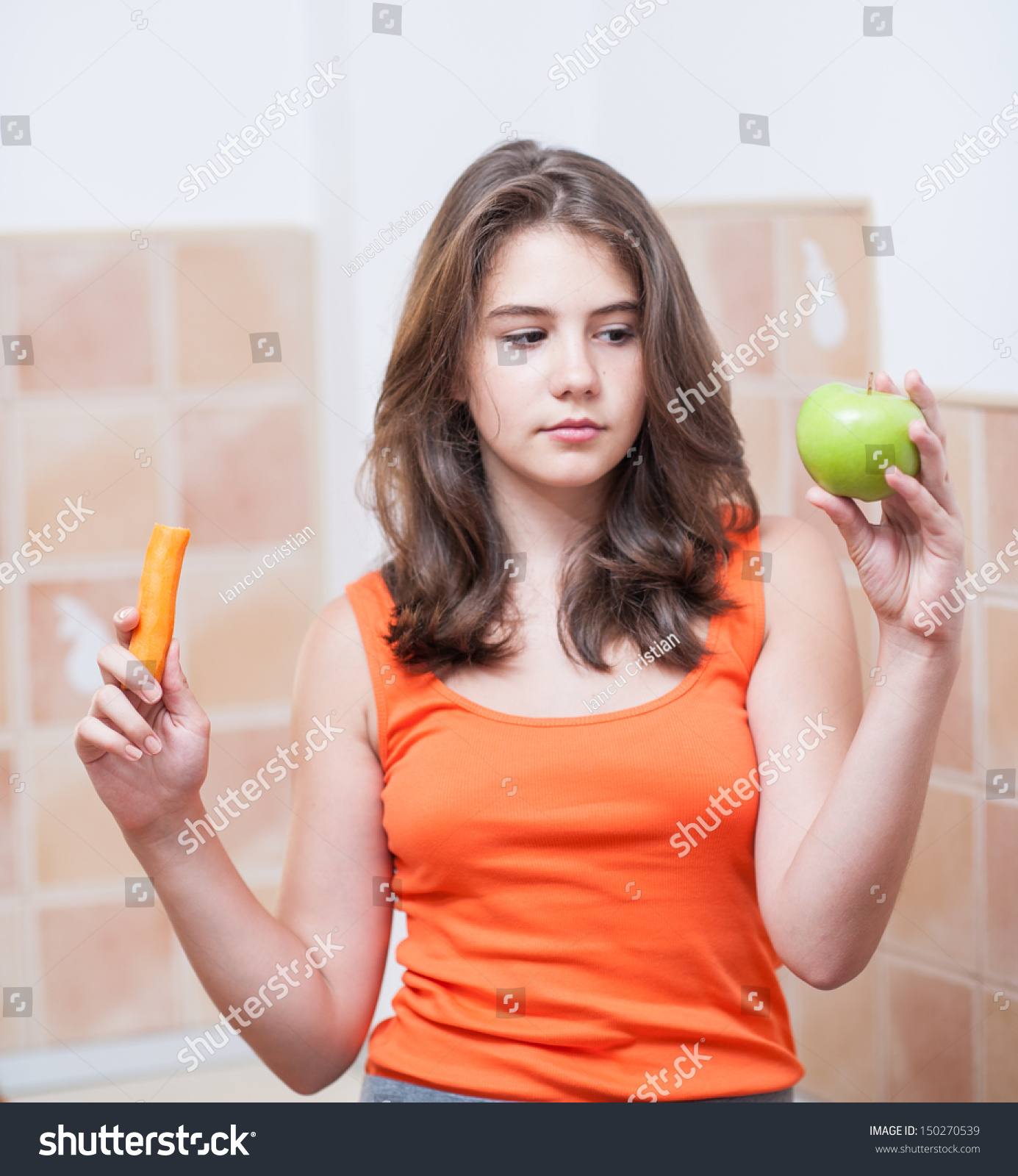 Pretty teen girl looking at a carrot and an green apple, indoor. Beautiful  teenage
