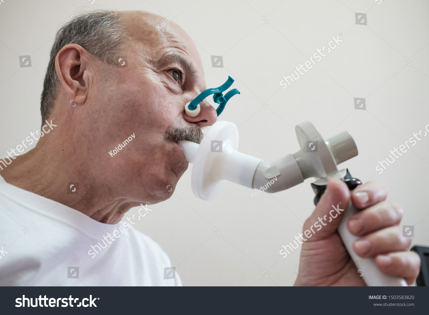 Senior hispanic man man testing breathing function by spirometry. Diagnosis of respiratory function in pulmonary disease