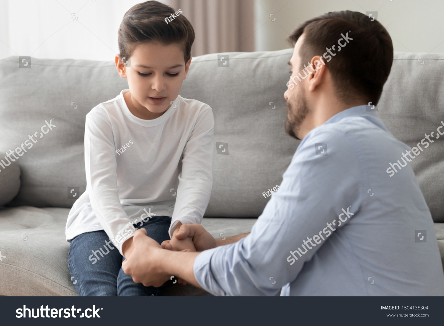 Worried loving young single father holding hand talking comforting upset little kid son sharing helping with problem, caring dad foster parent give support apologizing supporting listening child boy #1504135304