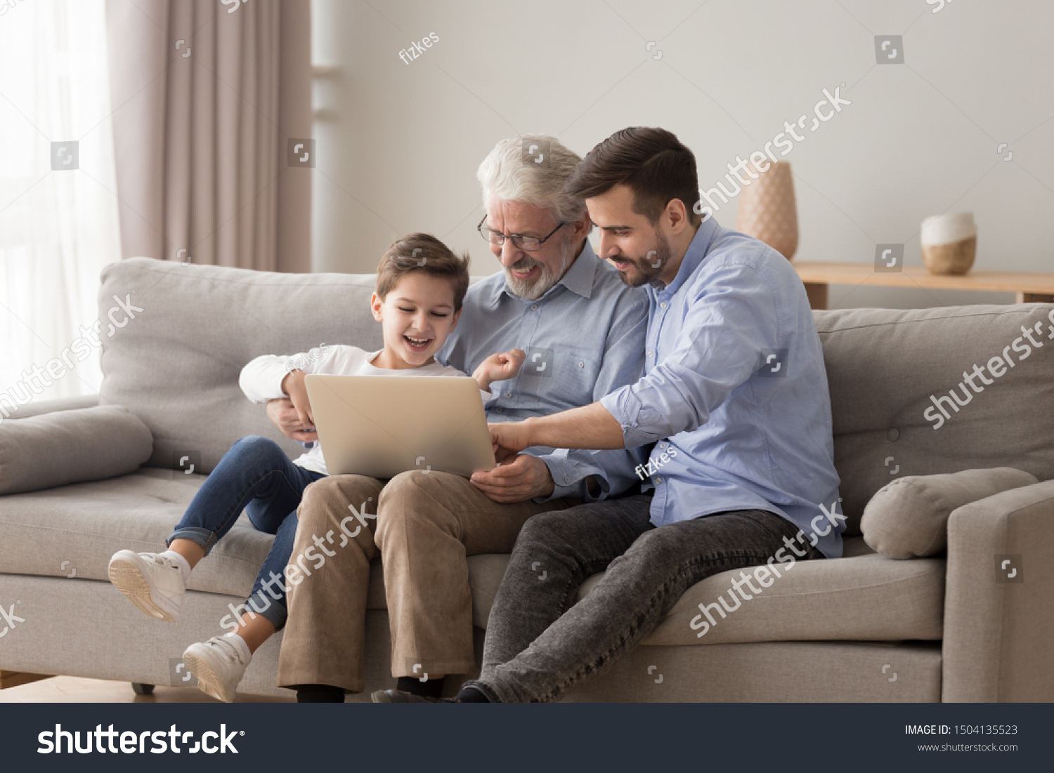 Happy three 3 age multi generation men family old grandfather young adult grown son father and child boy grandson having fun using laptop computer spend time browsing internet at home sit on sofa #1504135523