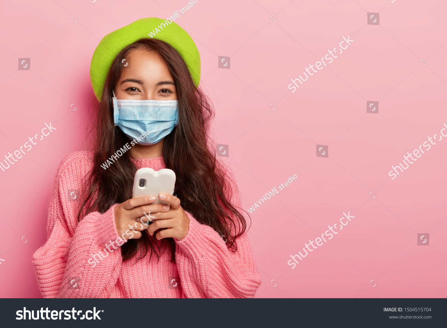 Satisfied mixed race woman has flu, wears protective medical mask not to infect other people, uses cell phone for surfing internet, reads how to cure disease online, dressed in fashionable clothes #1504515704