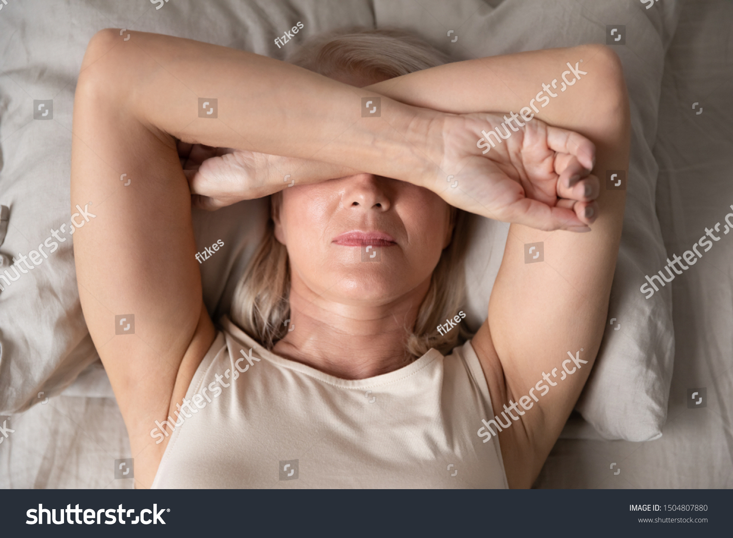 Sleepless mature woman suffering from insomnia close up, lying in bed, older female covering eyes with hands, trying to sleep, nightmares or depression, feeling headache or migraine #1504807880