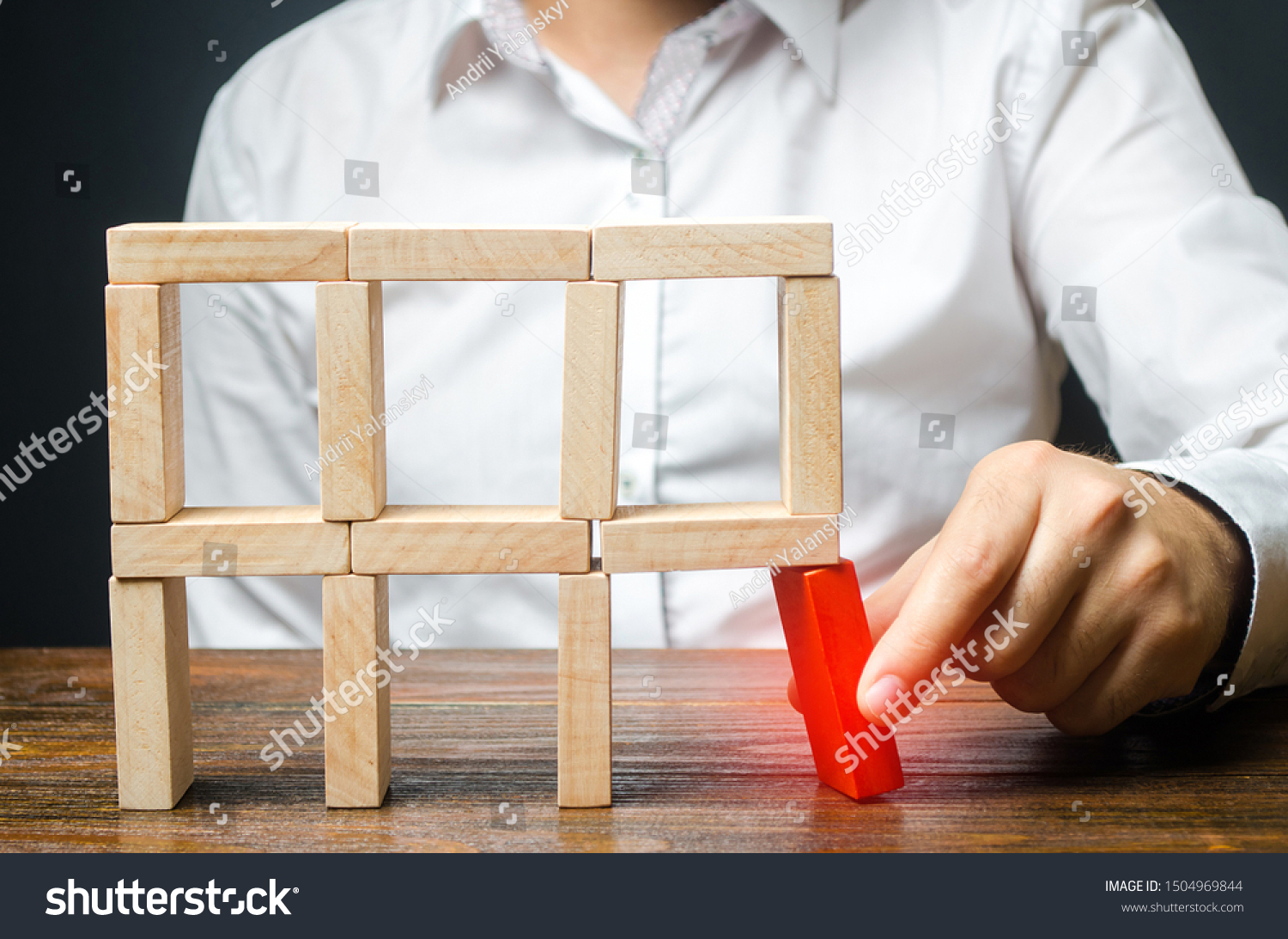 The man removes the red structural element, which will collapse. Incompetent businessman. Loss of key elements and employees. Damage to the opponent. Destruction of a complex structure by negligence. #1504969844