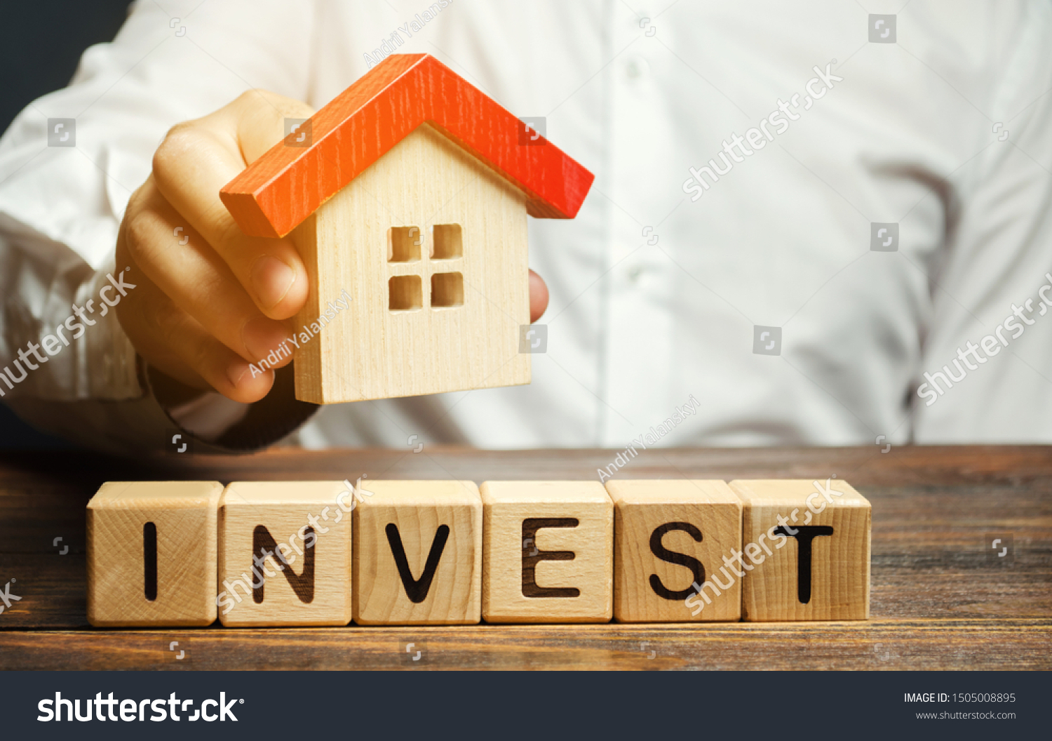 Wooden blocks with the word Invest and house in the hands of a businessman. The concept of investing in real estate construction. Effective investment. Buying apartments. Business and finance #1505008895