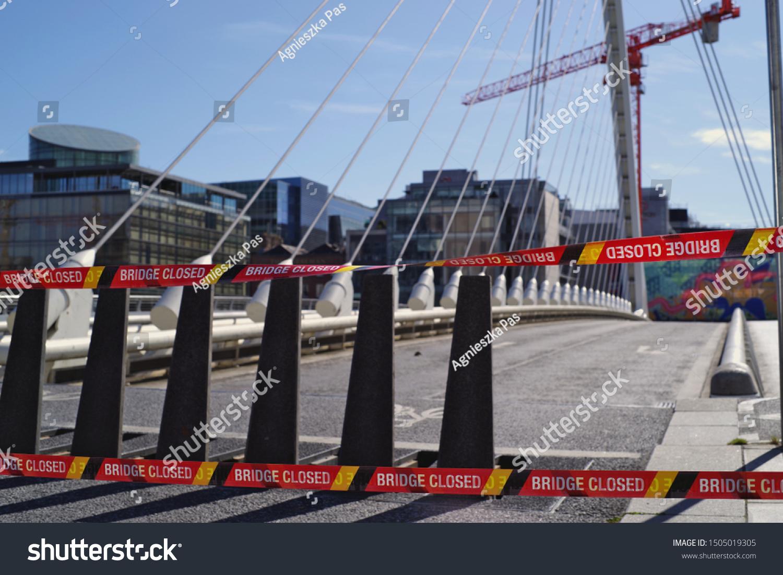 "DUBLIN, IRELAND - SEPTEMBER 14, 2019: View of the Samuel Beckett bridge just after closing for scheduled maintenance. ""Bridge closed"" warning tapes in main focus. Horizontal view."