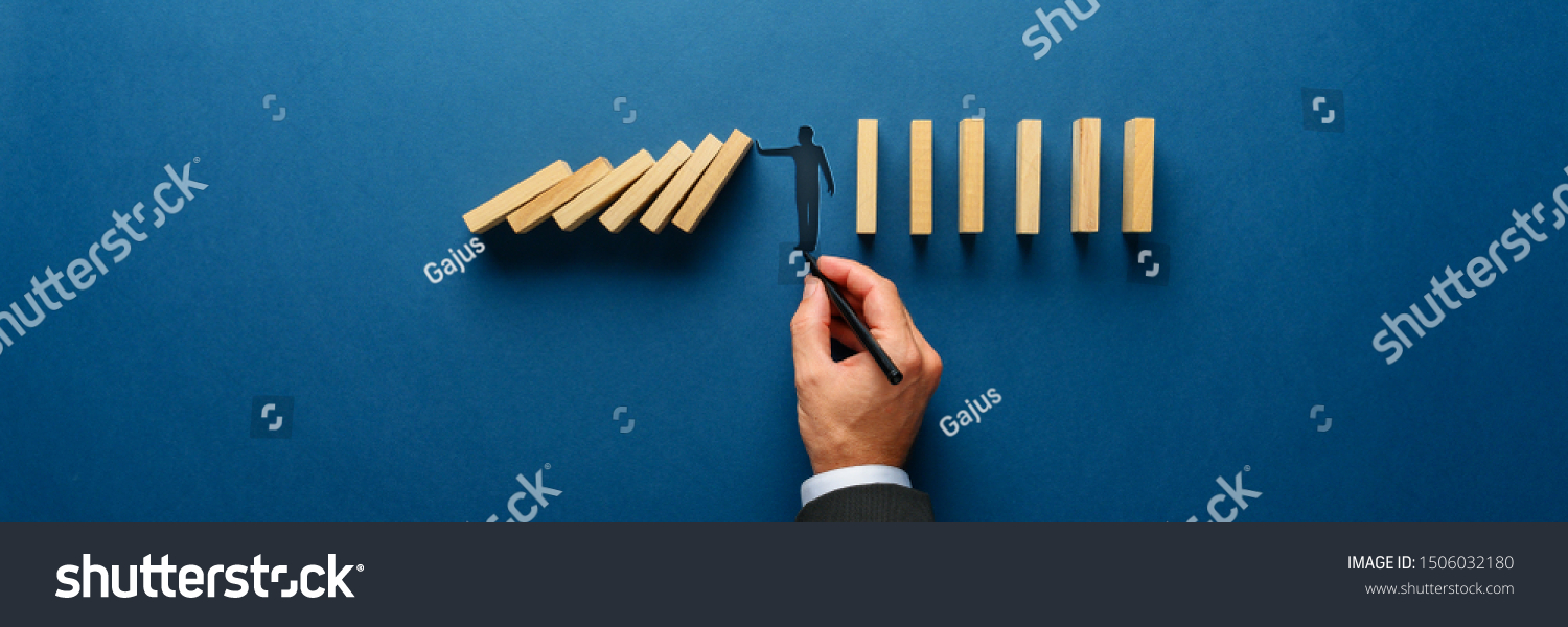 Wide view image of male hand drawing silhouette of a man making a stop gesture to prevent wooden dominos from collapsing. Over navy blue background. #1506032180