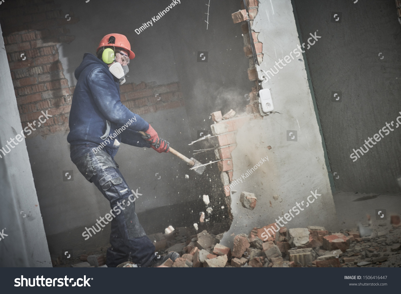 demolition work and rearrangement. worker with sledgehammer destroying wall #1506416447