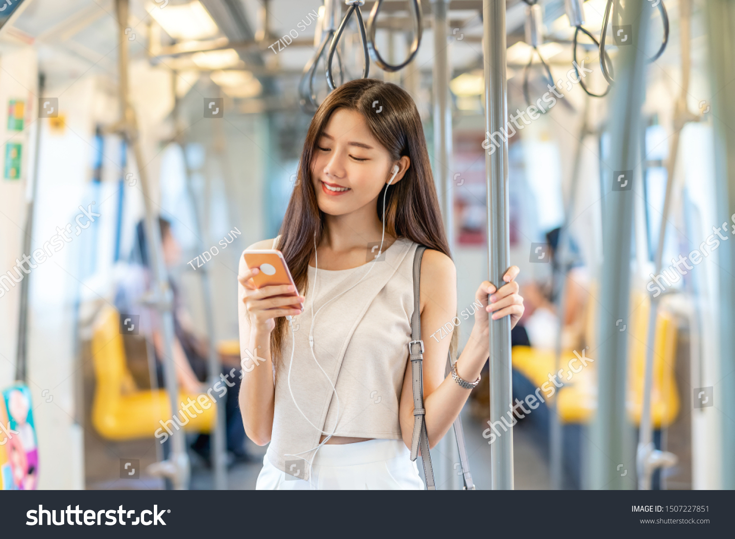 Young Asian woman passenger listening music via smart mobile phone in subway train when traveling in big city,japanese,chinese,Korean lifestyle and daily life, commuter and transportation concept #1507227851