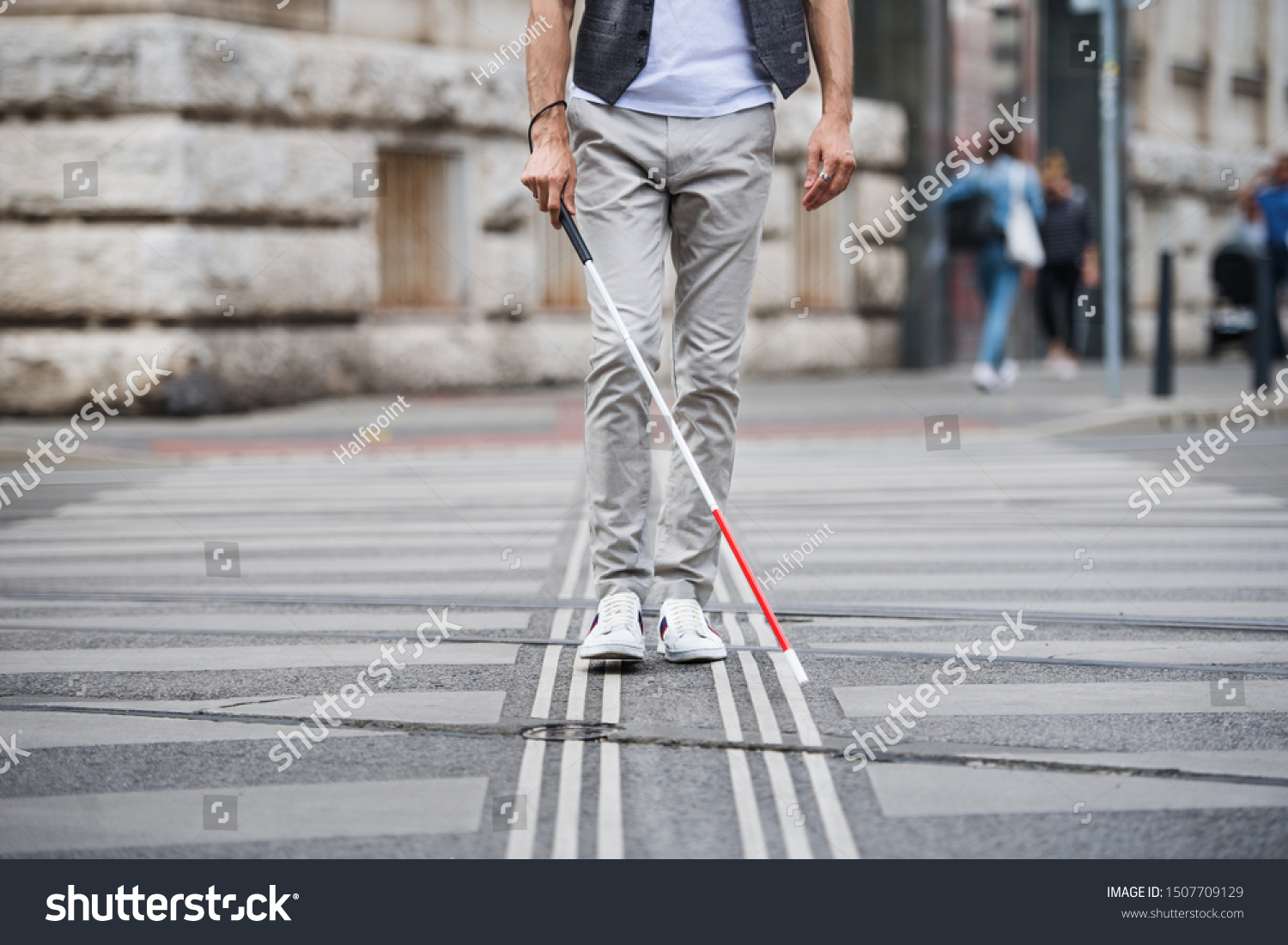 Midsection of young blind man with white cane walking across the street in city. #1507709129