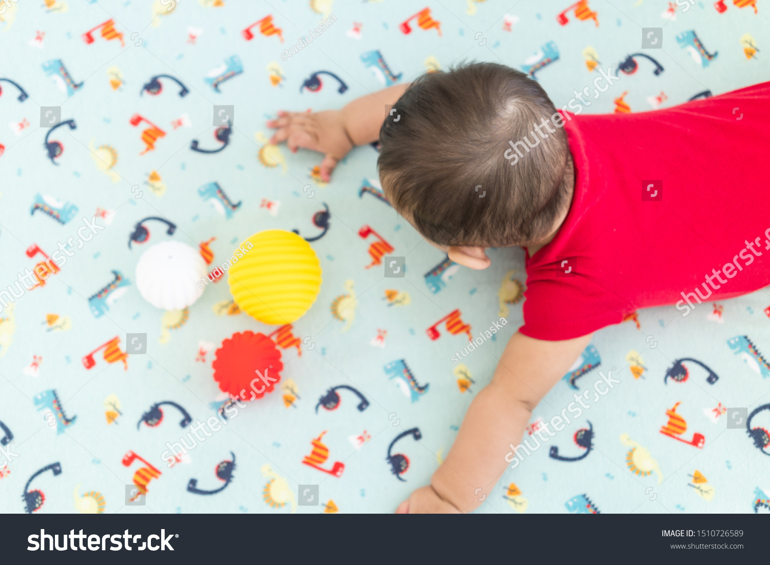 Baby playing with colorful toy rubber balls in the crib in a bright room. Child wearing a red bodysuit, laying on playful dinosaur crib sheet. #1510726589
