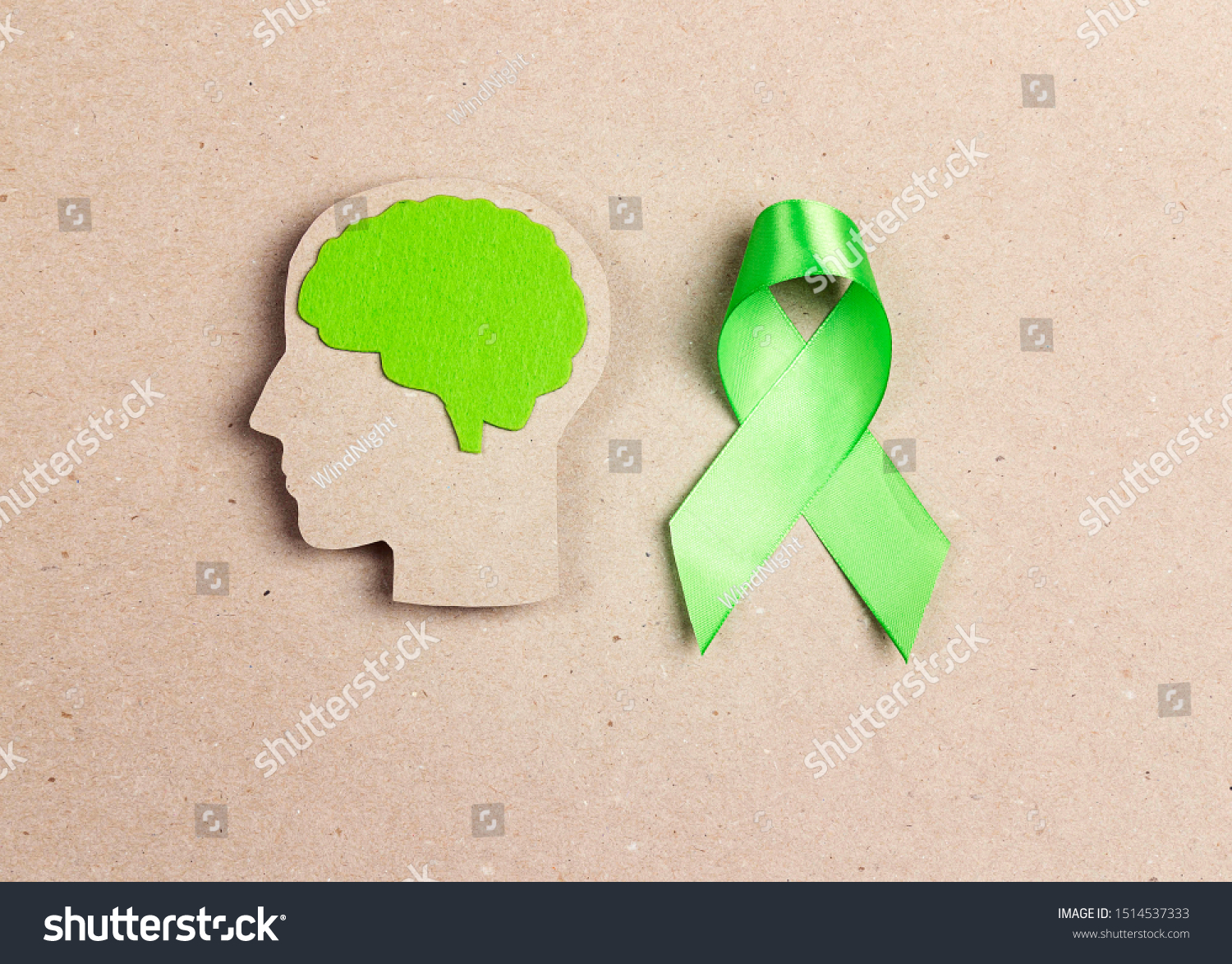 World mental health day concept. Green awareness ribbon and brain symbol on a brown background.
