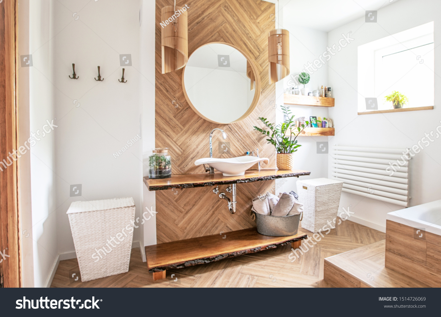White sink on wood counter with a round mirror hanging above it. Bathroom interior. #1514726069