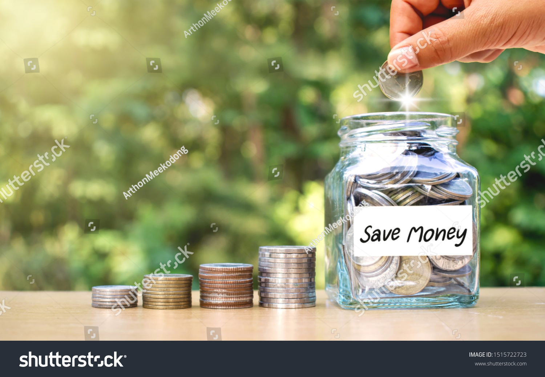 Hands Are Putting Money In A Jar Of Money Money Saving Ideas