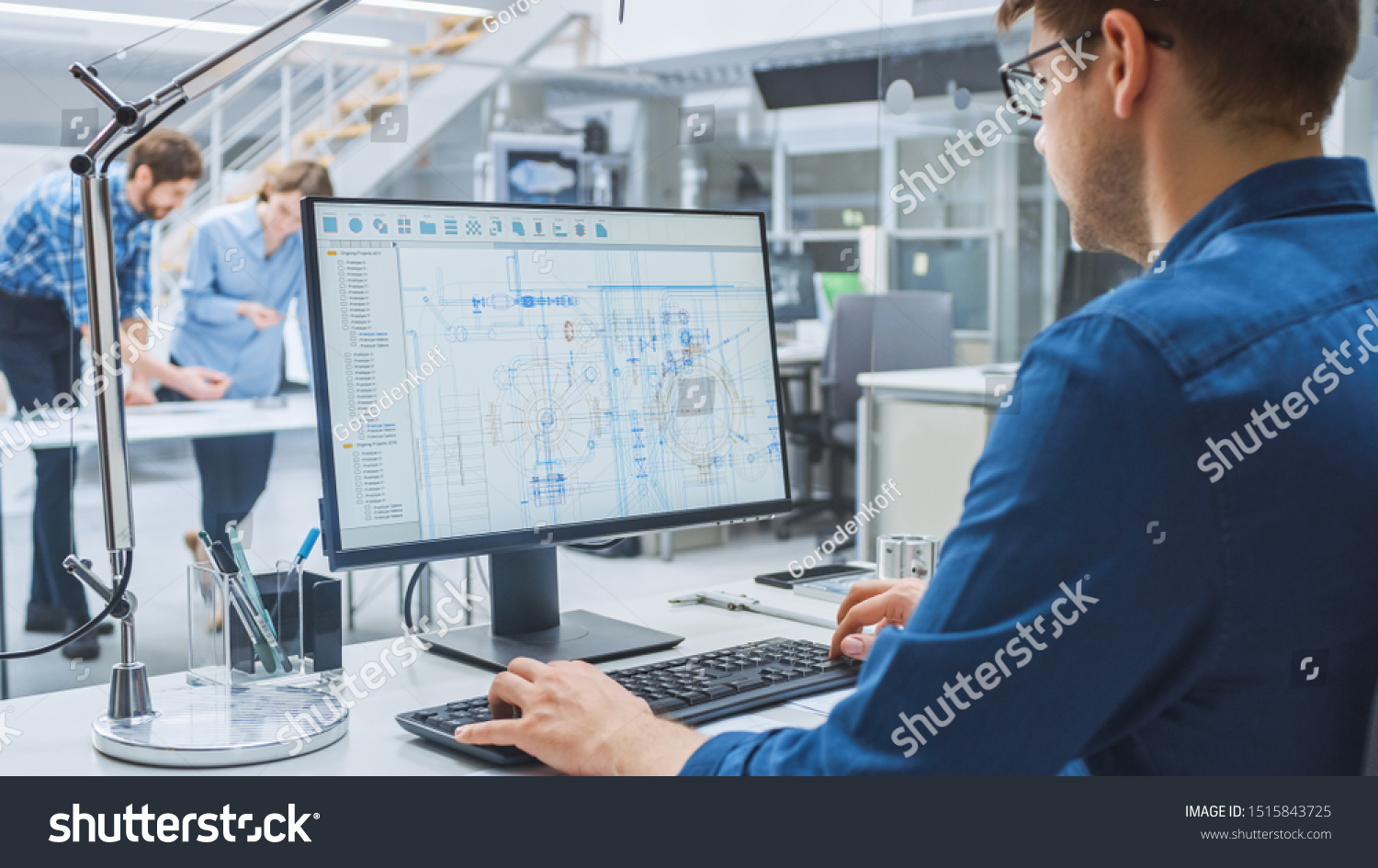 Over the Shoulder Shot of Engineer Working with CAD Software on Desktop Computer, Screen Shows Technical Drafts and Drawings. In the Background Engineering Facility Specialising on Industrial Design #1515843725