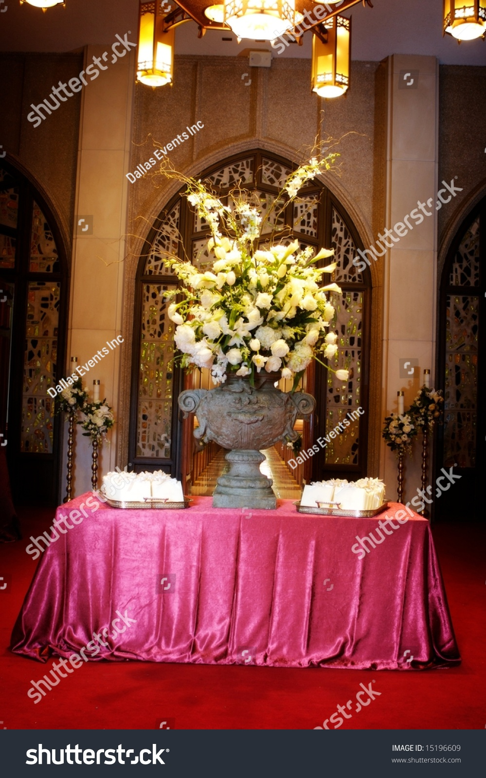 An Image Of A Luxurious Table Setting With Large Flower Arrangement And Wedding Programs