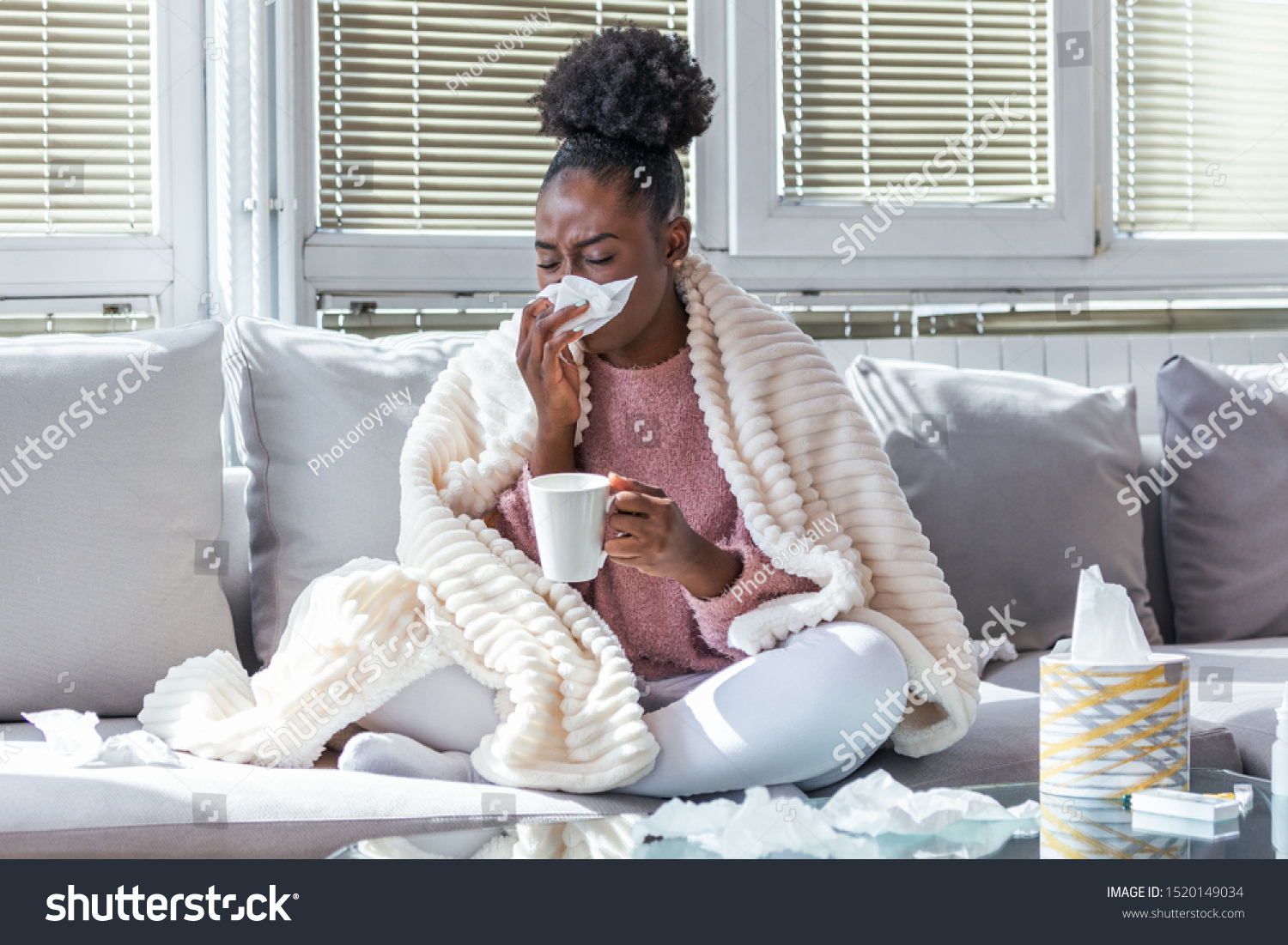 Sick day at home. African American woman has runny nose and common cold. Cough. Closeup Of Beautiful Young Woman Caught Cold Or Flu Illness. Portrait Of Unhealthy Girl Drinking Tea. #1520149034