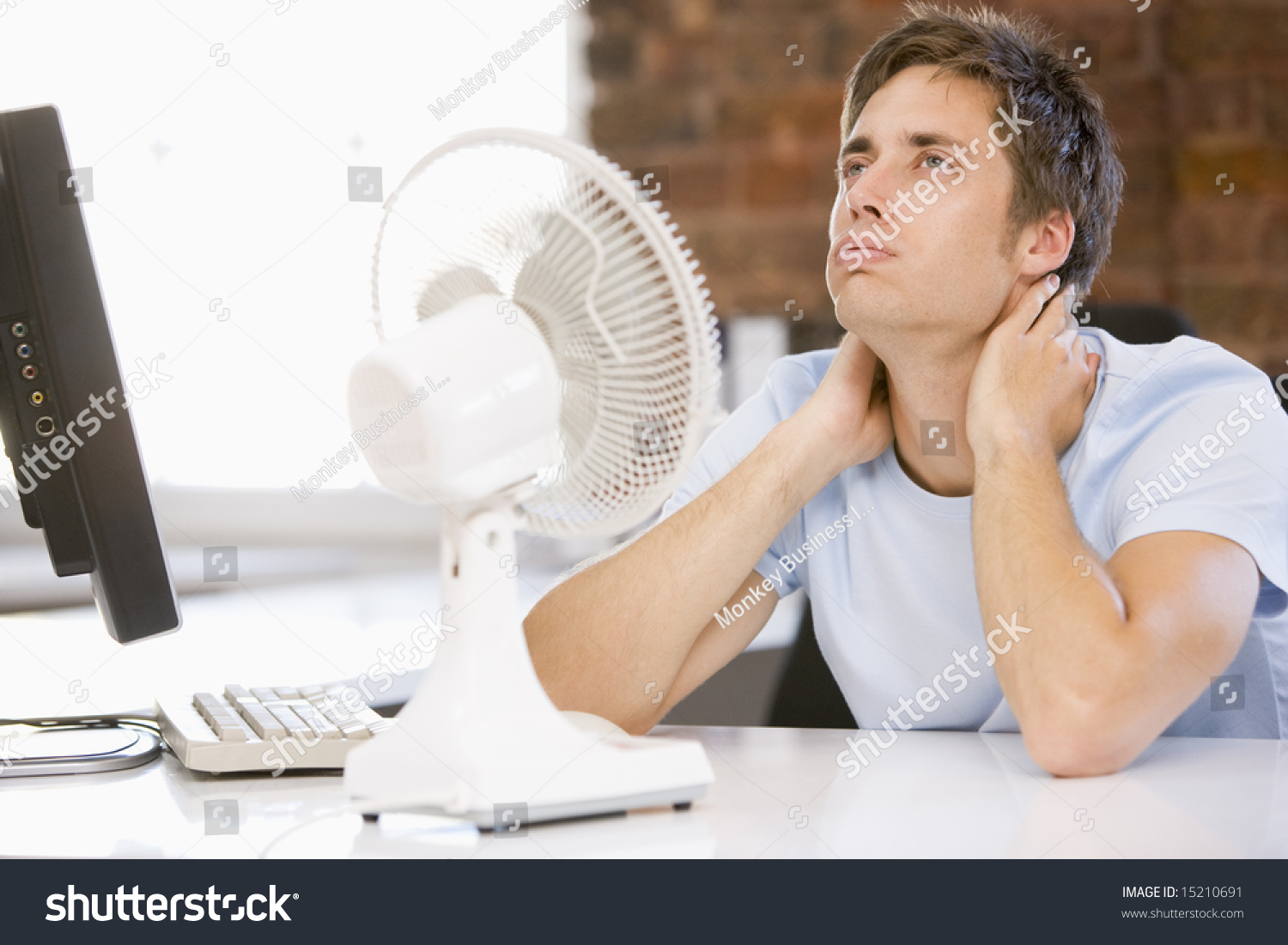 Cooling Off With Fan : Businessman in office with computer and fan cooling off