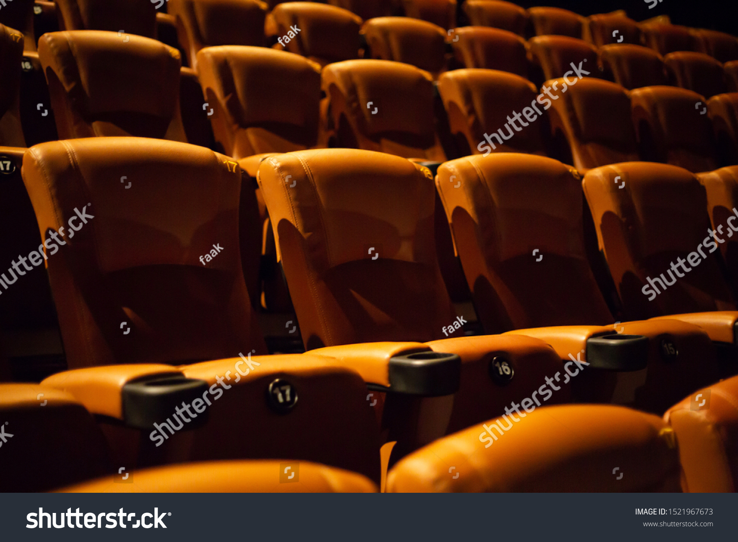 brown special leather seat in movie theater. pattern of many armchairs in dark room . #1521967673