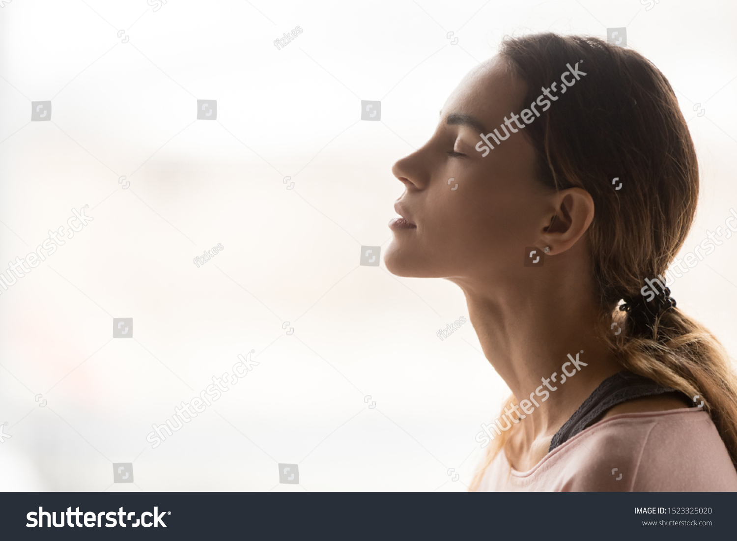 Serene young woman taking deep breath of fresh air relaxing meditating with eyes closed enjoying peace, calm girl tranquil face doing yoga pranayama exercise feel no stress free relief, side view #1523325020