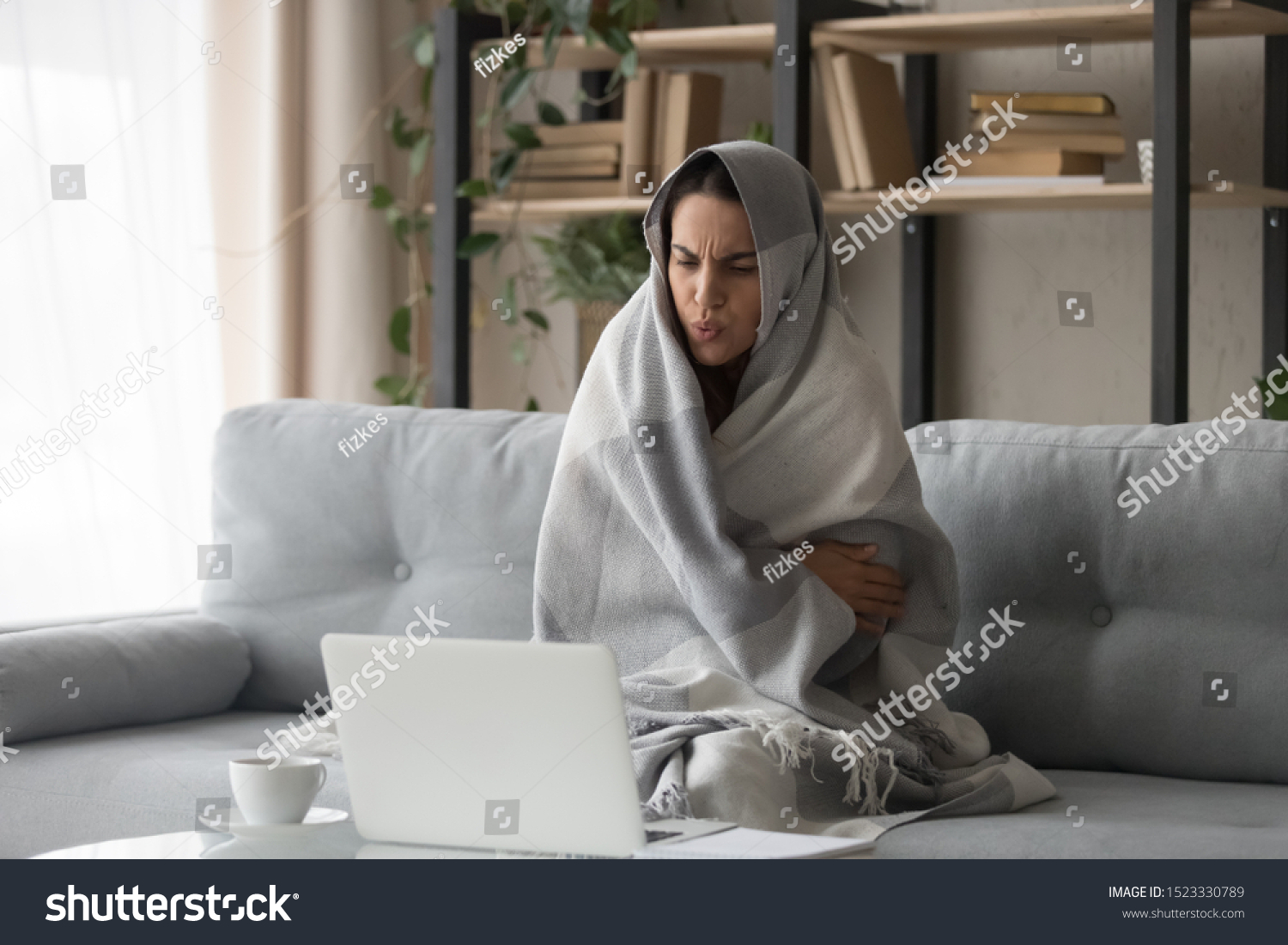 Sick ill young woman feel cold covered with blanket sit on sofa watching movie on laptop, annoyed girl shiver freezing warming at home wrapped with plaid, no central heating problem and flu concept #1523330789